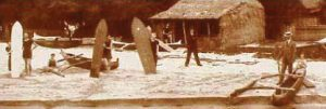 An old sepia photograph of people holding surfboards on the beach. In the background is a grass building and to the right is a wooden outrigger canoe.