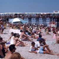 An old photograph of a large group of people on the beach with the pier in the background.