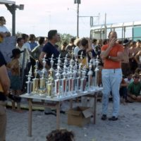 A group of people on the beach gathered around a table with many trophies on it.