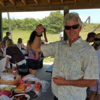 A man in sunglasses attending a grill and holding up a hotdog. In the background are people at picnic tables.