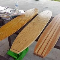 Wooden skateboard decks laid out over a picnic table.