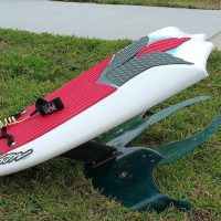 A red and white hydrofoil board on the grass.