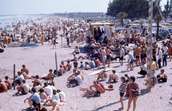 An old photograph looking down at a large group of people on the beach