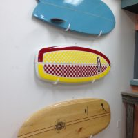 Three paipo boards mounted on the museum wall. The top one is blue with fins. The middle is red and yellow checkerboard pattern. The bottom one is wood with central stripes running the length of the board and a turtle illustration on it.