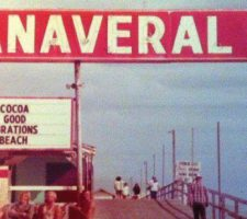 Historical Photo of Canaveral Pier with the pier extending into the distance. At the top, a large red and white sign reads: Canaveral Pier. On the left, a smaller black and white sign reads: COCOA GOOD VIBRATIONS BEACH. On the right is a Ron Jon Surfing Shop sign.