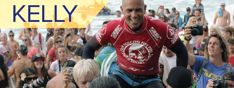 Kelly Slater being carried on peoples' shoulders with a crowd and the ocean in the background