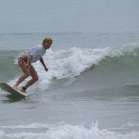 A woman surfing in a white shirt