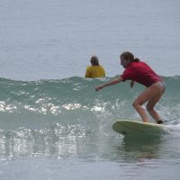 A woman surfing in a red shirt