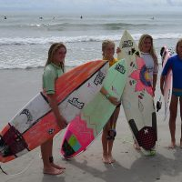 Four girls holding surfboards posing for a picture in front of the ocean