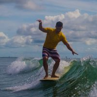 A man in yellow shirt and striped trunks riding a wave