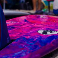 A photo of the underside of a surfboard with a blue pink and purple marbalized pattern