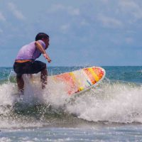 A man in a purple shirt and dark trunks surfing